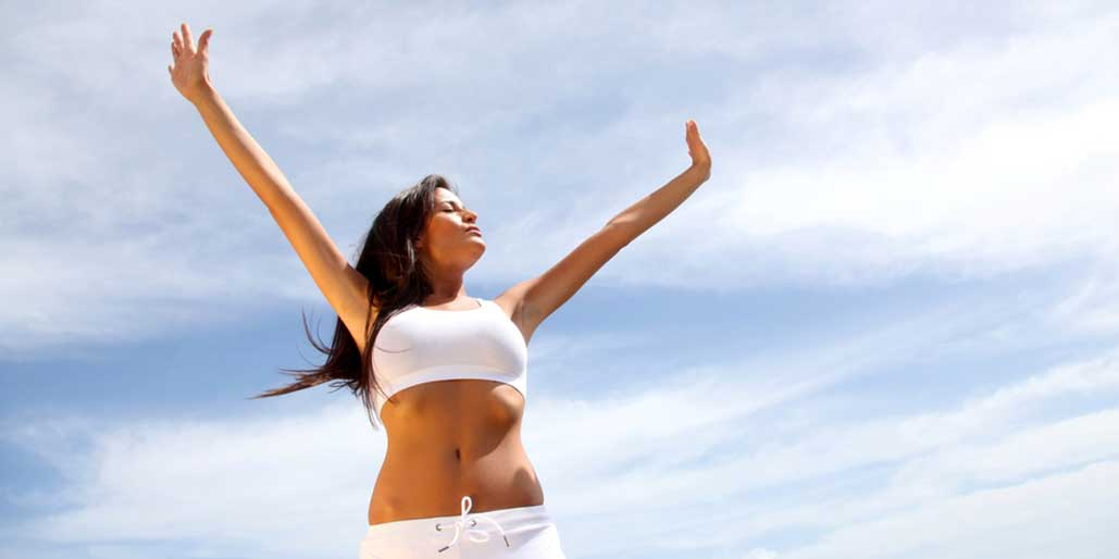 Woman with arms raised in sun.